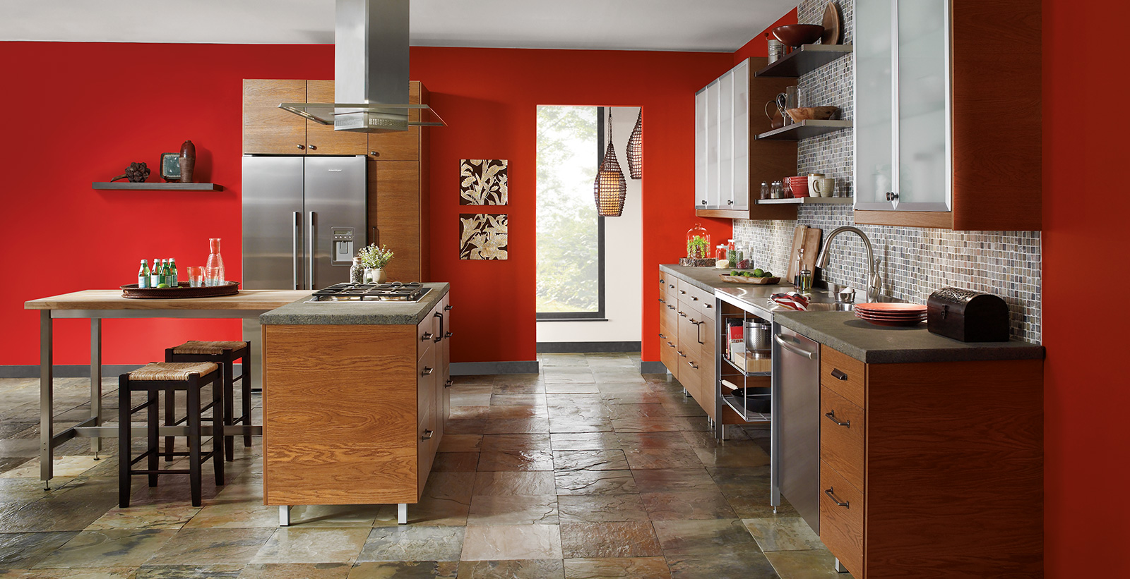 Eclectic styled kitchen with deep red on walls, wooden cabinetry, and stone flooring.