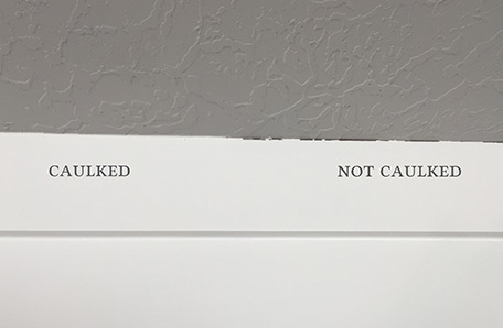 Painted wall showing the difference between caulked and uncaulked seams