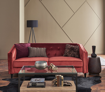 Living room with red couch and beige walls with modular accent feature.