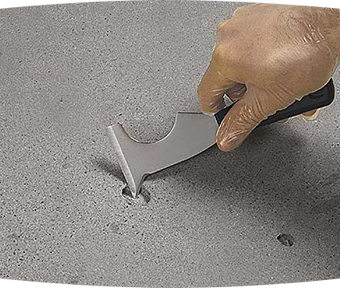 Person holding a tool repairing a hole in concrete