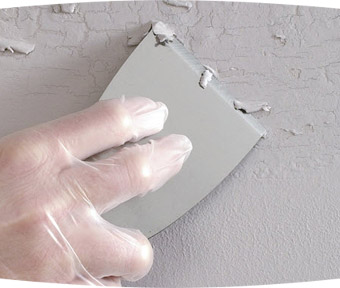 Person repairing peeling paint on wall