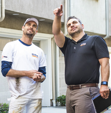 A BEHR PRO Rep pointing at a building while a Pro Painter is looking at what he is pointing.