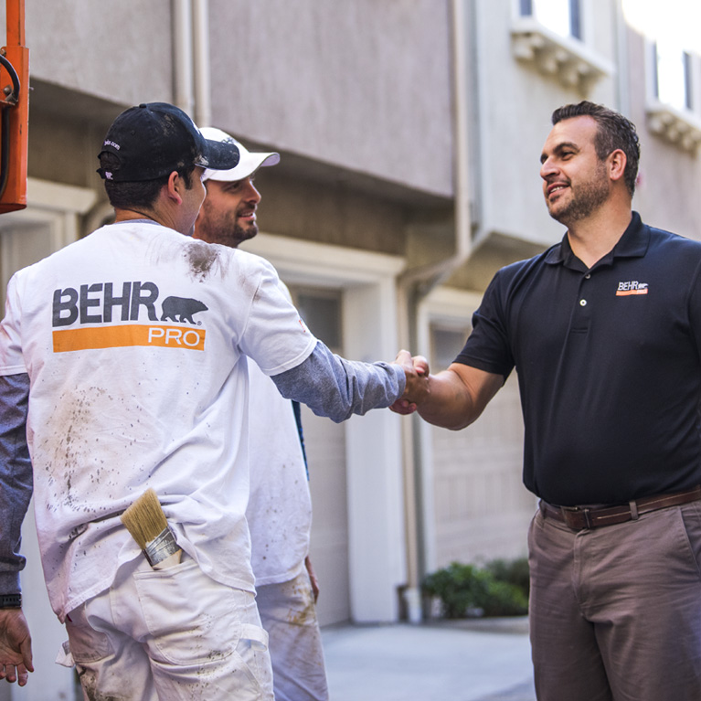 A mobile view of a BEHR PRO Rep shaking hands with on of the 2 Pro Painters. In the background is a multi family condo units.