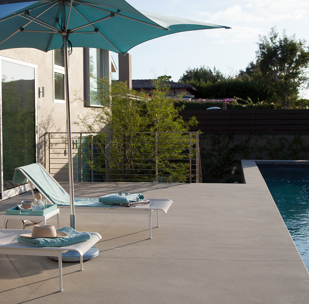 Two pool chairs and umbrella sitting aside a pool