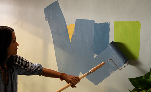 Person rolling blue paint on a wall